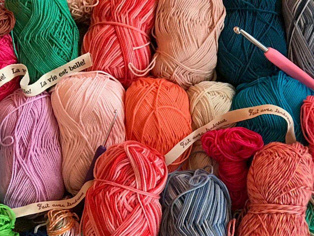 Ensemble de pelottes de laines de différentes couleurs avec crochet et ruban