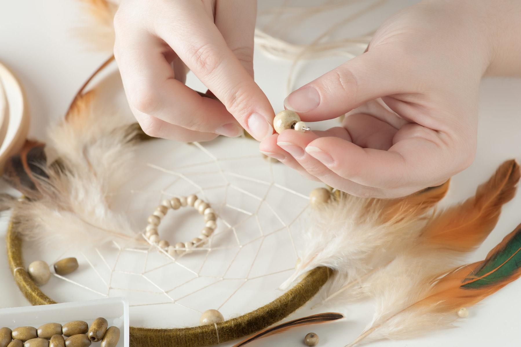 Gros plan des mains féminines avec des perles en bois, ayant assemblé le capteur de rêves. Composition d'atelier artisanale de plumes, perles, fils, outils pour le bricolage