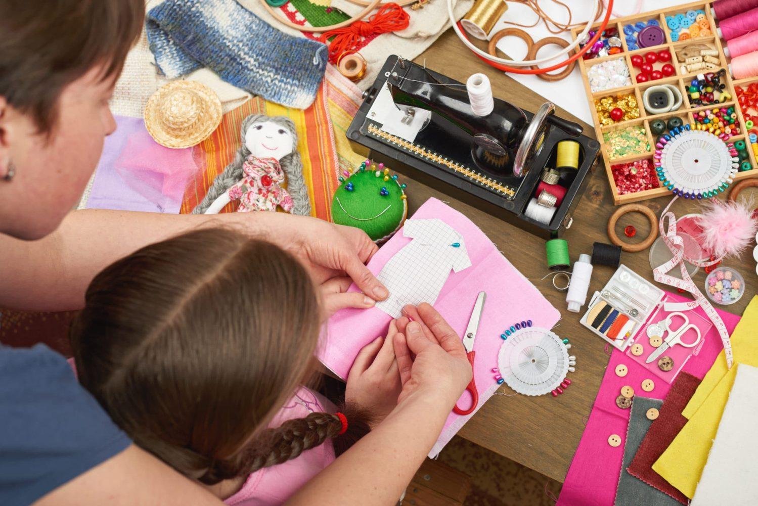 atelier couture parent-enfant mère apprenant à sa fille à coudre une poupée à partir d'un patron. différents matériels de couture, bouture, fil, cisaux, tissus