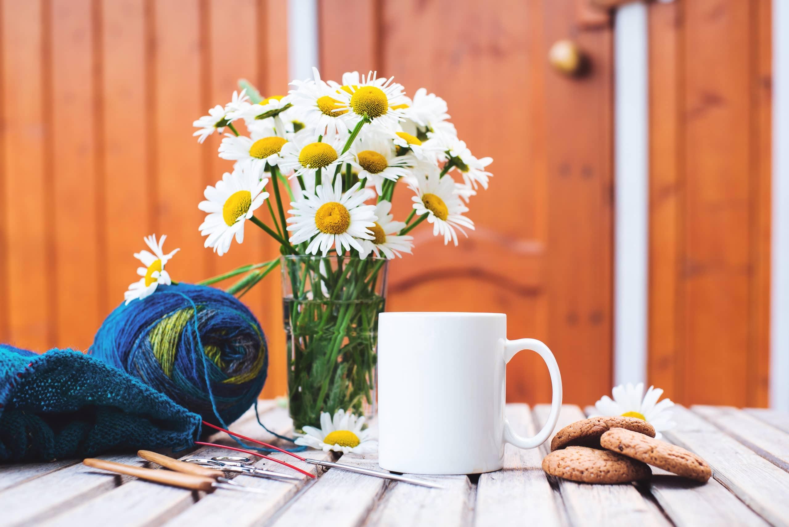 passe-temps de femmes. Crochet et tricot. Espace de travail. Un bouquet de marguerites dans un vase, une tasse blanche avec une boisson, des biscuits, des boules de laine, des aiguilles, des ciseaux, des tricots, des crochets sur une table en bois dans une maison confortable.