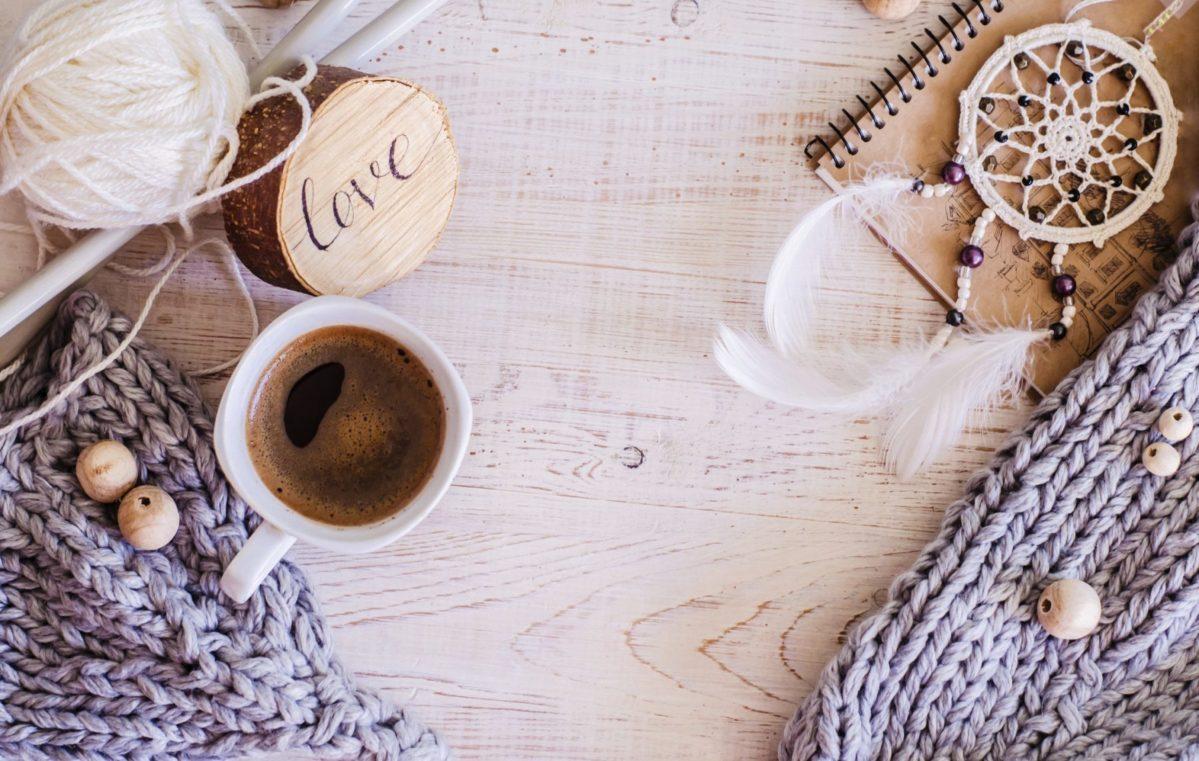 composition cozy avec tasse de café, éléments tricotés en laine mérinos sur fond en bois. Une photo dans un style Hygge.