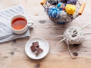 ne tasse de thé, des pelotes de laine, des aiguilles à tricoter et un drap de laine sur une table en bois marron. Travail manuel, hygge, time out.
