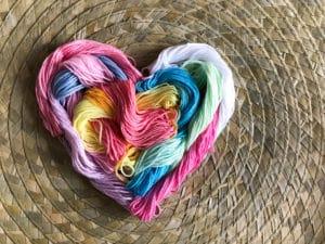 laine, fil coton mutlicolore formant un coeur dans arrière plan naturel