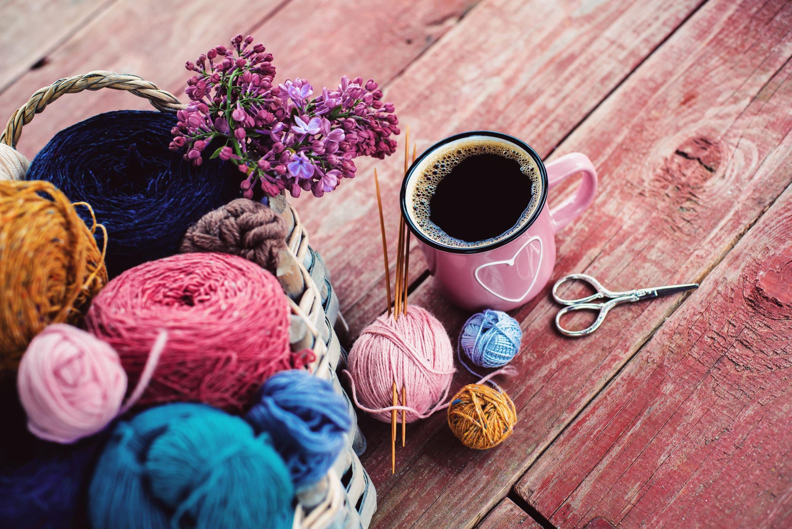Café crochet | Différentes pelotes de laine, fil avec aiguilles, ciseau et tasse de café, concept de bien-être, repos, sérénité