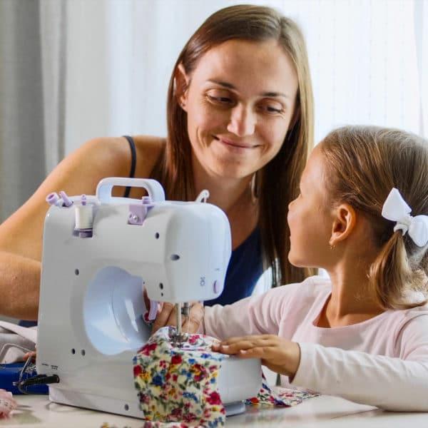 mère et fille devant une machine à coudre cousantn un bout de tissu