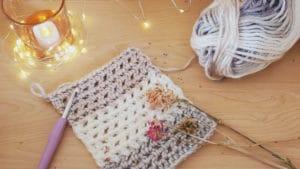 création au crochet, laine de couleur beige, crème avec bougie allumée, ambiance cosy, sereine, bienveillante, de repos