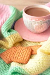 moment de détente avec tasse de café, petits biscuits et couverture en laine de couleur pastel