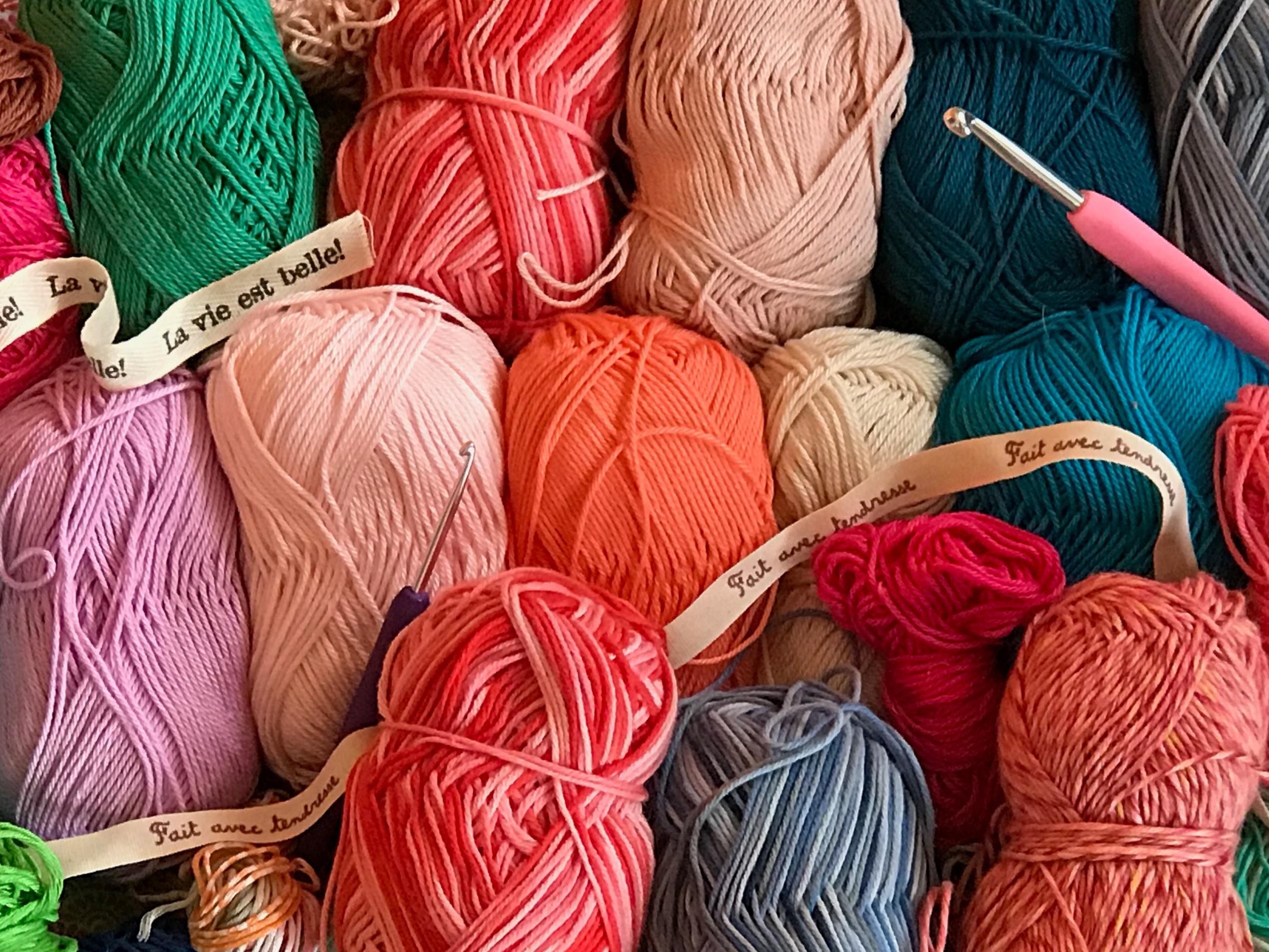 """Ensemble de pelotes de laine de différentes couleurs avec crochet et ruban """"la vie est belle"""" """"fait avec tendresse"""""""
